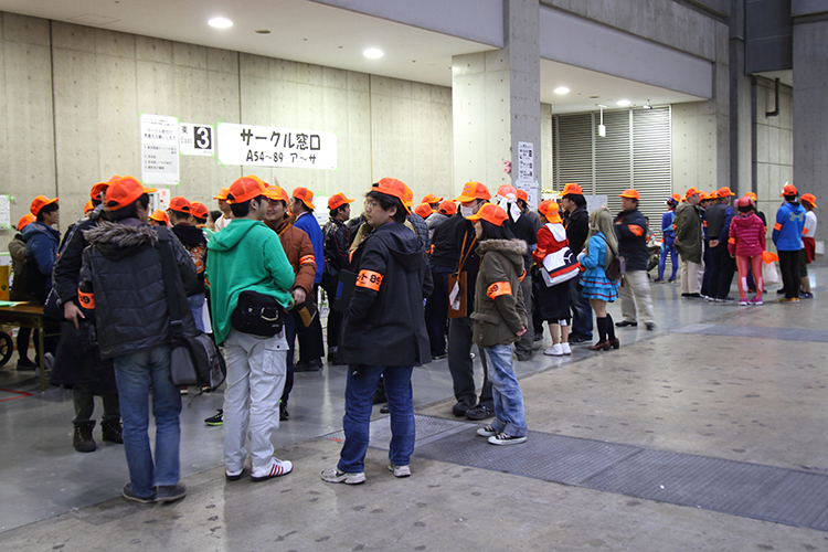 Comiket volunteers in orange caps and armbands