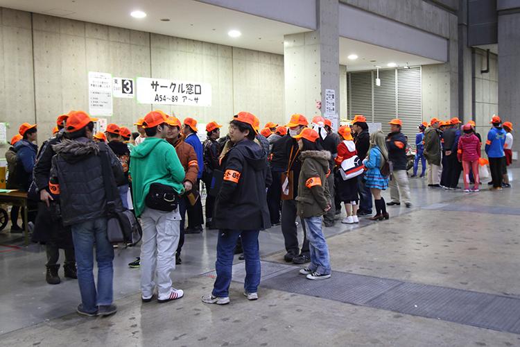 Comiket volunteers in orange caps and armbands