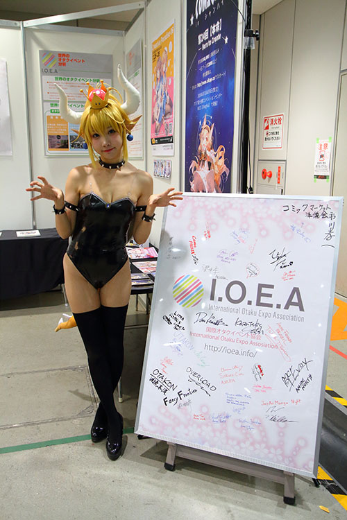 Cosplayer in Kuppa Hime (Bowsette) costume standing beside IOEA signboard with various signatures from representatives of events around the world.